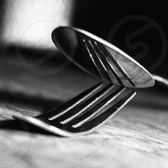 tip of fork beneath spoon photo