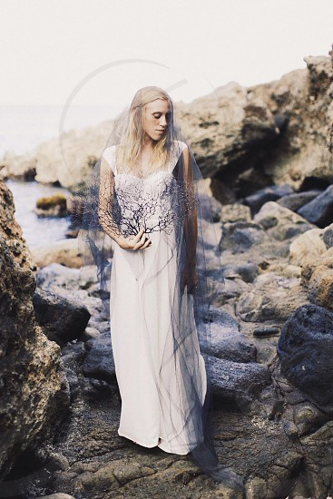 woman in white floor length gown standing on rocks by the sea photo