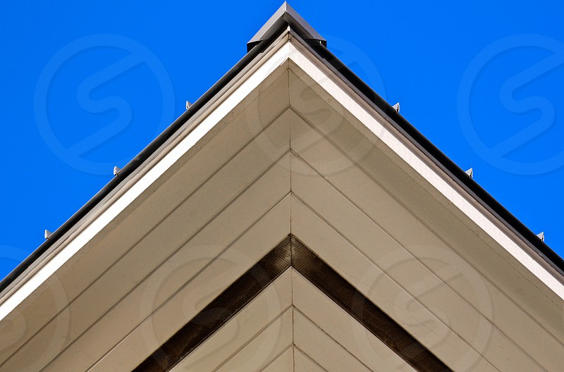 brown white and black wooden triangular roof under clear sky during daytime photo