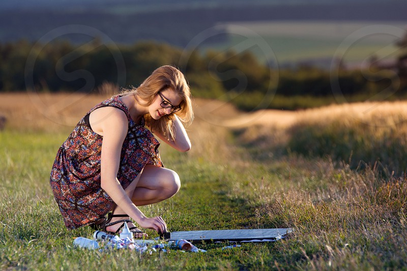 Young lady draws painting in nature. photo