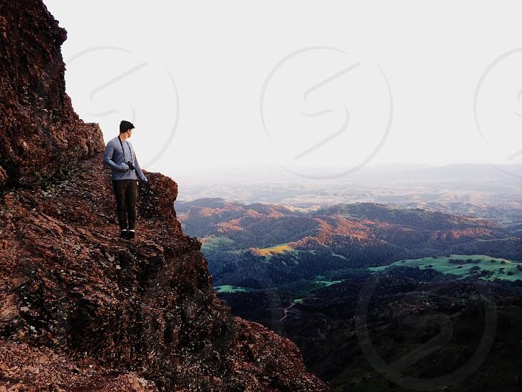 man in blue shirt standing at hillside photo