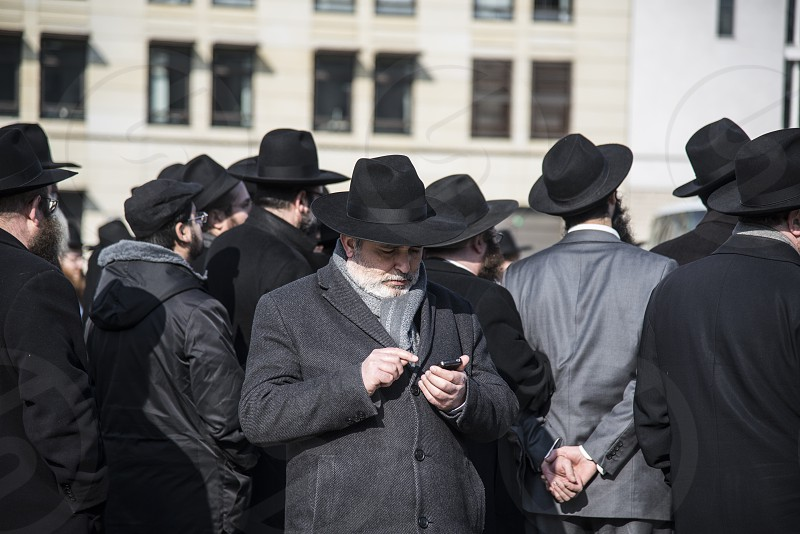 A man using his phone behind a crowd of men photo