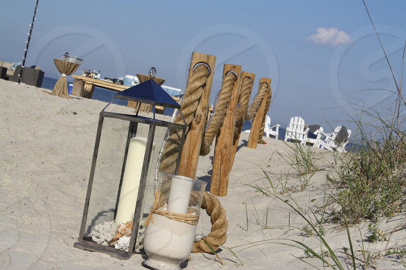 tall lantern and hurricane glass candle holders on beach by rope photo