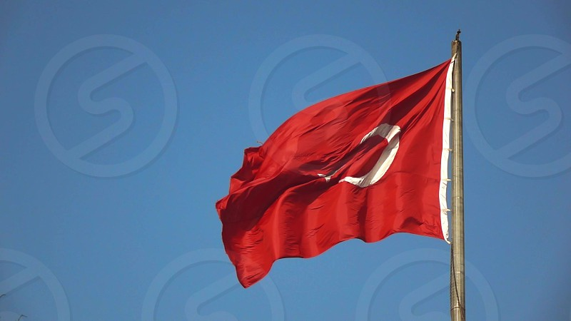 Turkish red flag fluttering on the wind in the blue sky with image of white star. National symbol of the state Turkey. Slow motion Full HD video 240 fps 1080p. photo