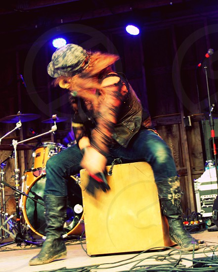 Girl beats on wooden box during concert photo