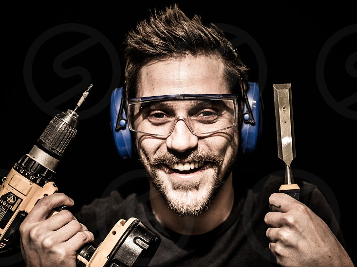 Carpenter portrait shot in studio with black backdrop holding a drill and chisel next to his head and wearing safety goggles and ear protectors photo