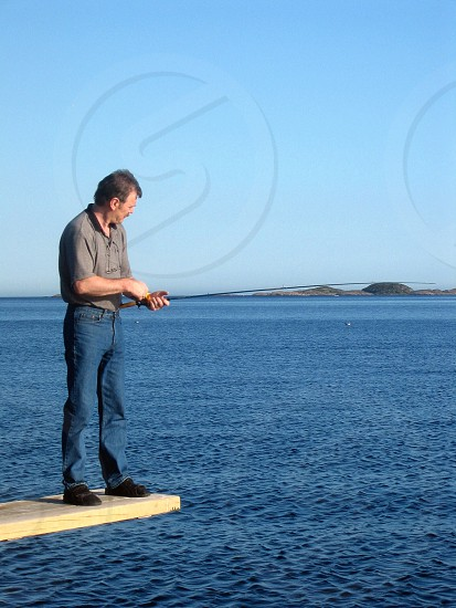 man holding fishing rod photo