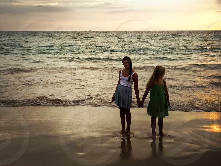 2 women standing on seashore photo