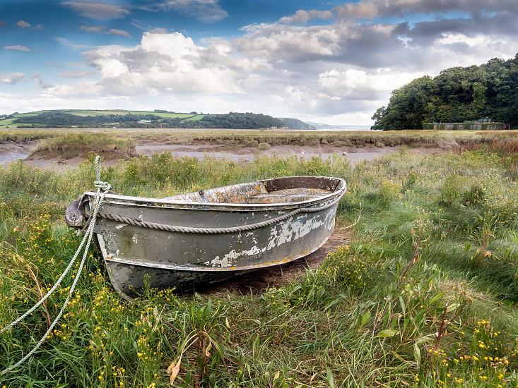 The Grey Boat at Laugharne. A small grey boat moored on the estuary beside the castle at Laugharne Carmarthenshire Wales. photo
