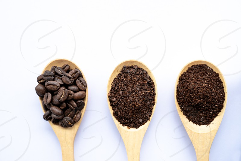 top view wooden spoons filled with coffee bean and crushed ground coffee  on white background photo