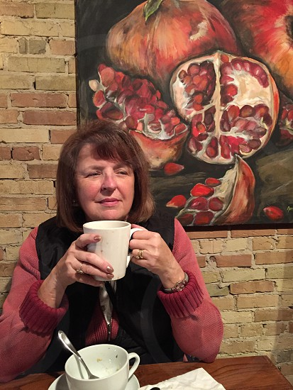 A mature woman looks off wistfully holding cup of coffee stunning colors and art photo