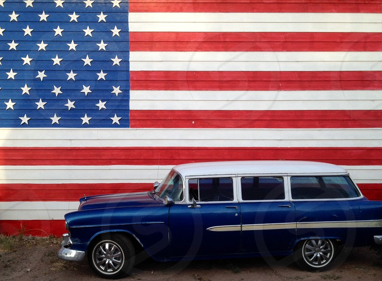 blue classic car besides American flag painted wall photo