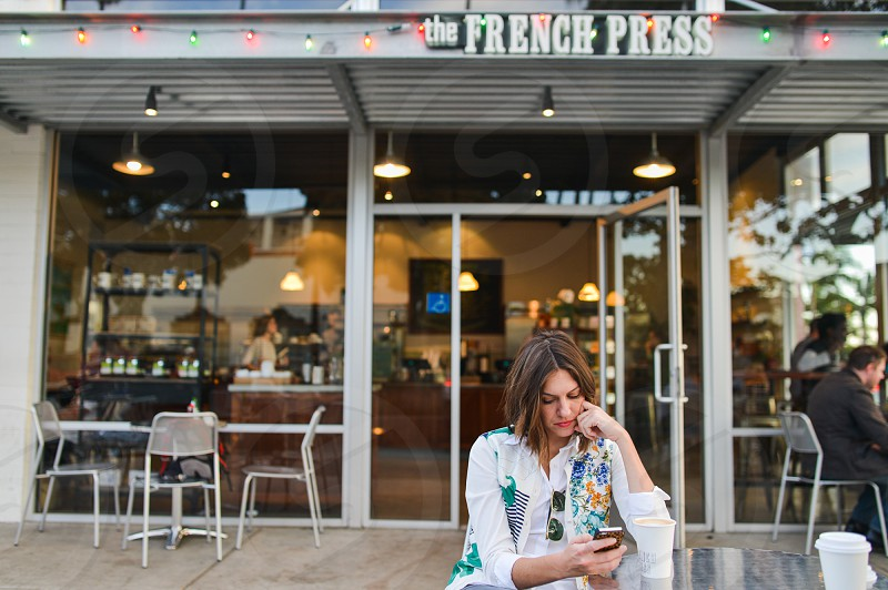 woman in white blue long sleeved shirt in front of the french press store photo
