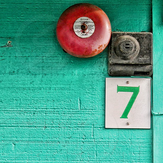 The numeral '7' hangs near a red fire alarm bell. photo
