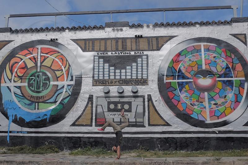 man doing jump flip near DJ controller painted wall at daytime photo