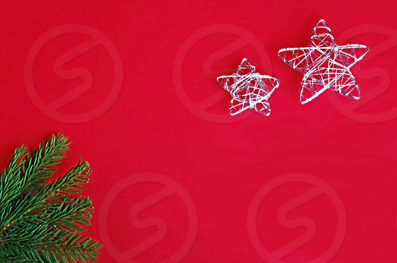 red christmas background with green spruce branch shiny silver colored wire stars and copy space photo