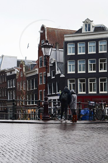 Traveling couple looking over canal bridge at Amsterdam's historic city center row houses. photo