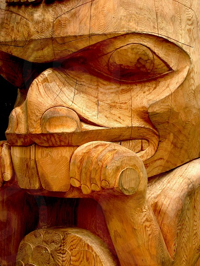 Natural (non-painted) Totem showing wood and human carved patterns. Beaver face closeup. Location: Prince Rupert BC Canada. photo