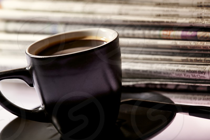 Cup of coffee and pile of newspapers on the table. photo