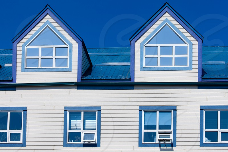 Exterior detail of frame building upper story windows and two dormers in blue metal roof photo