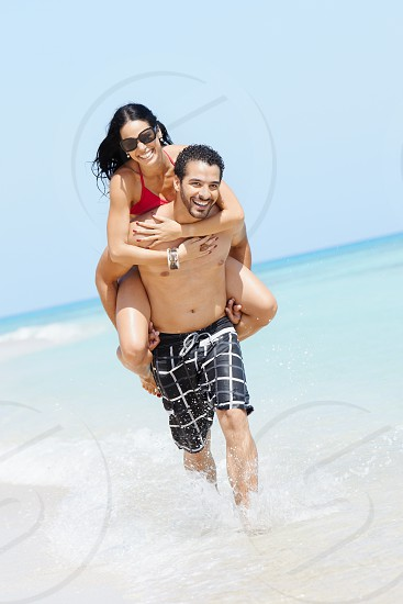 people; piggyback; shore; running; sea; couple; cuba; 30s; active; adult; away from it all; back; beach; beachwear; bikini; boyfriend; caribbean; carrying; copy space; enjoying; happiness; happy; hispanic; holidays; honeymoon; husband; joy; latina; laughing; leisure; man; married; ocean; persons; playful; playing; ride; riding; shoulders; smiling; summer; swimsuit; tourism; tourist; travel; tropical; vacations; water; wife; woman photo