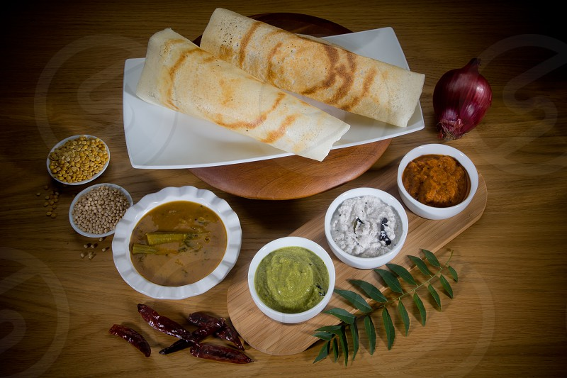 An Indian food photo - this is Dosai with Sambar and the 3 Chutneys are Coriander Coconut and Tomato which the Dosai is dipped into when eating. photo
