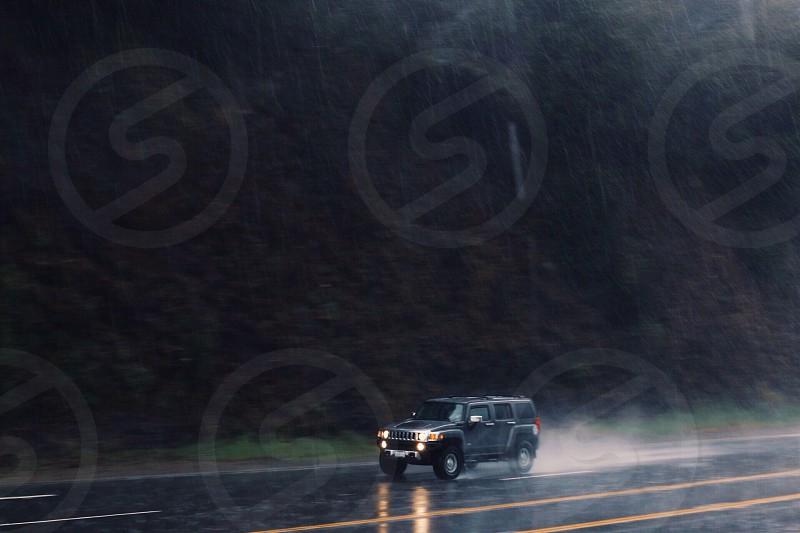 black hummer h3 speeding on gray concrete road near mountain while raining photo