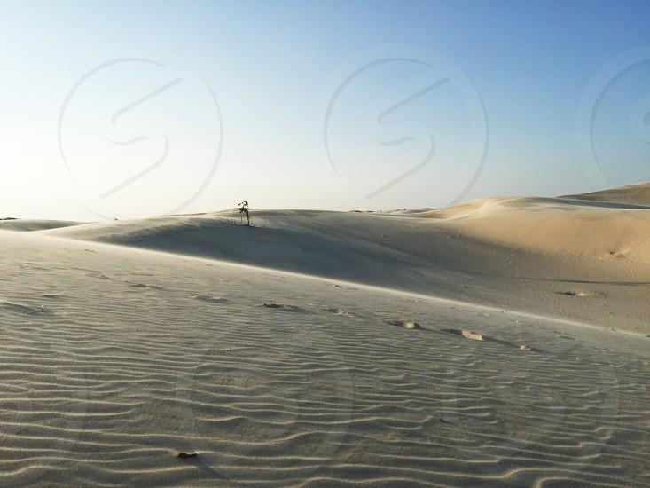 white rippling sand dunes during daytime photo