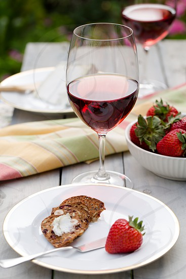 red strawberry sliced cookie and stainless steel cake slicer on white ceramic round saucer near clear wine glass with liquor and bunch of strawberries on a white ceramic bowl on brown table photo