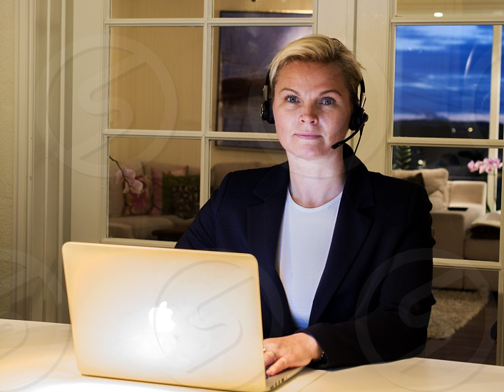 woman in white shirt black blazer with black headpiece working on apple laptop at white desk photo
