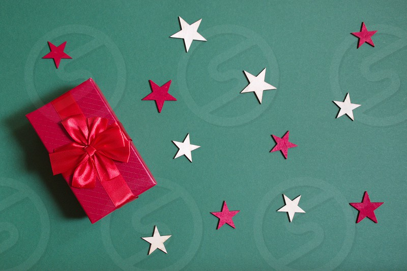 Flat lay of red Christmas gift and star shape against the green background photo