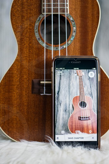 Picture in picture of ukulele in background and on cell phone photo