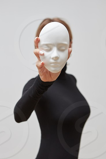 Girl in a black jumper hold plaster gypsum sculpture instead of face on a white background place for text. Concept The masks we wear. photo