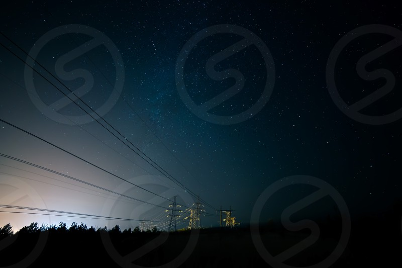 Incredible night sky with stars Milky Way passing over power line in long exposure timelapse. Beautiful panorama view. Nature in the countryside. Astro photography. photo