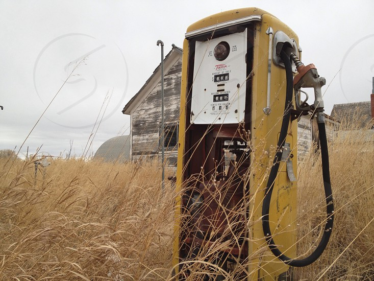 yellow gasoline pump station surrounded by brown grasses nearby house photo