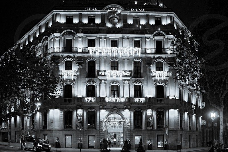 A black and white photo of a night building beautifully lit by garlands of lights. photo