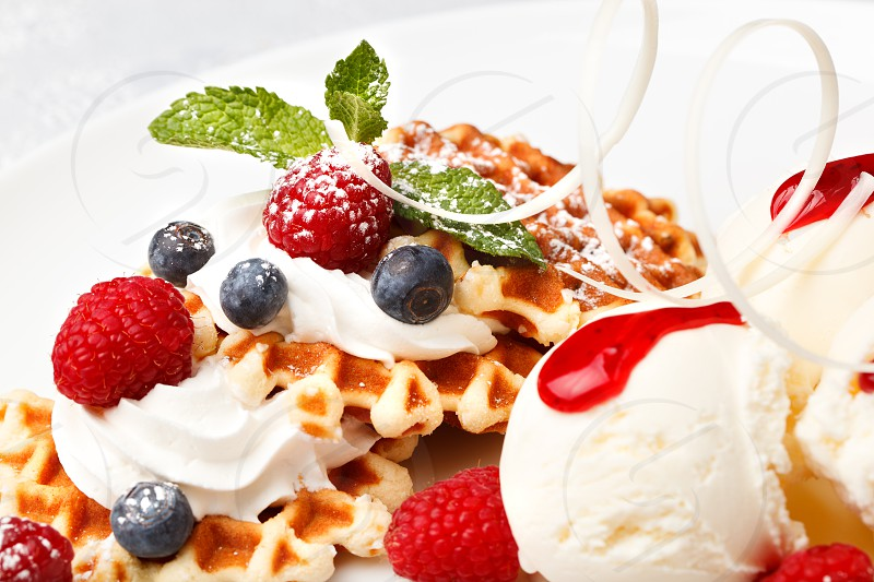 Crisp golden waffle topped with whipped cream served with scoops of vanilla ice cream and fresh raspberries and blueberries close up view photo