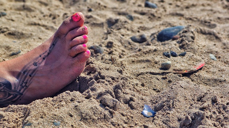 person with black stars foot tattoo on brown sandy beach photo