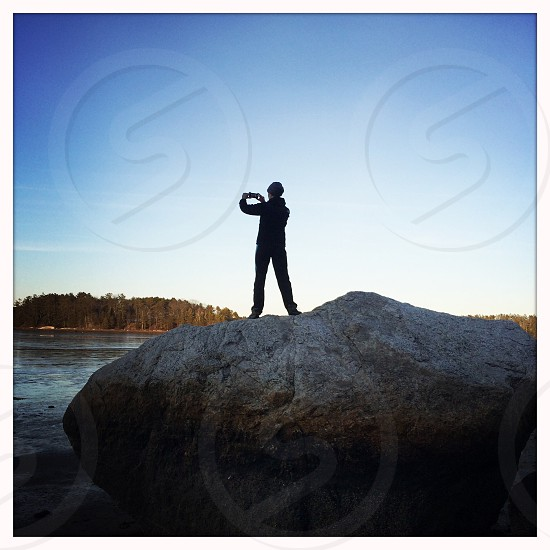 view of man standing on rock taking a picture photo