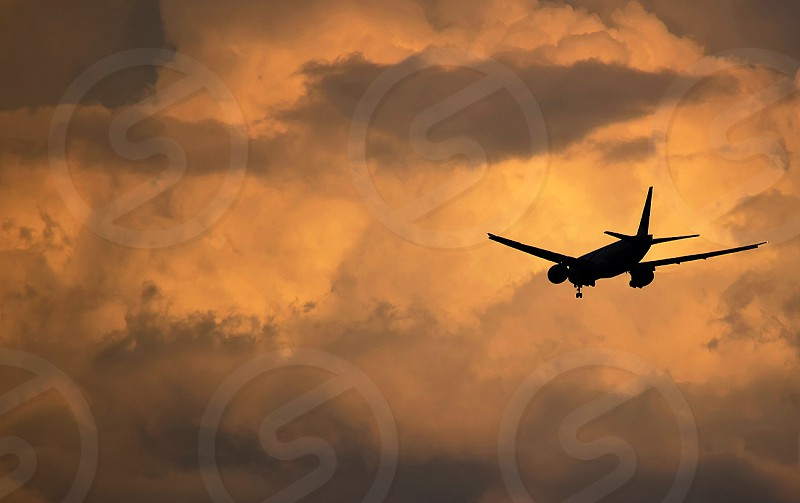 A Boeing 777-300ER on approach against a threatening formation of cumulus clouds at dusk. photo