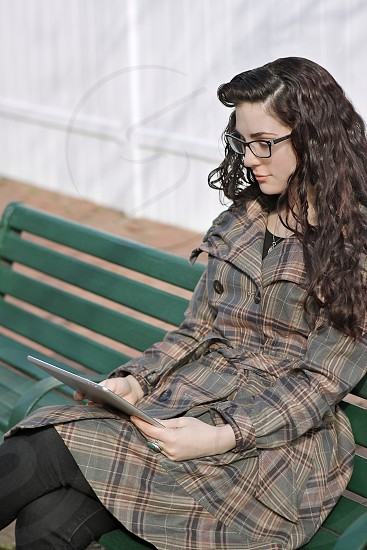 young woman sitting on a park bench using a tablet photo