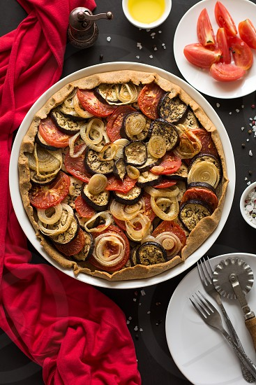 Homemade vegetable pie (galette) with grilled eggplants tomatoes and onion on brown wooden background. Selective focus photo
