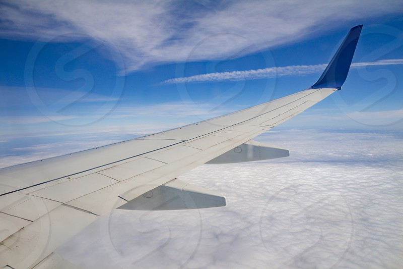 Airplane wing on the sky and over sea with clouds. photo