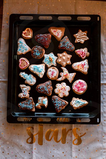 Christmas gingerbread cookies in many shapes decorated with colorful frosting sprinkle icing chocolate coating toppers put on tray photo