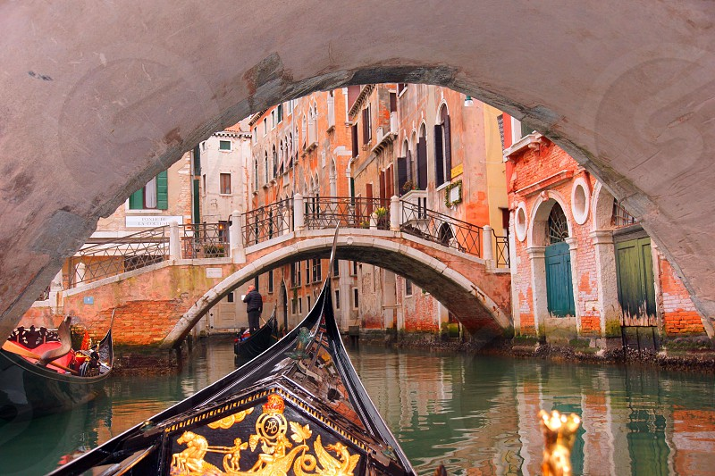 boat under concrete bridge in venice photo