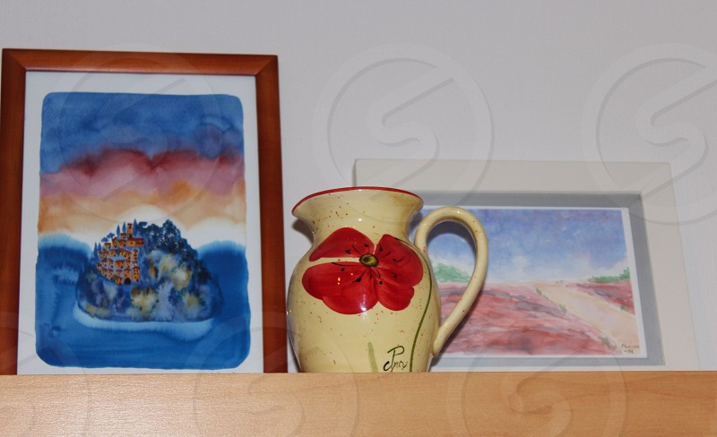 yellow and red floral ceramic pitcher beside brown wooden framed island painting on brown wooden rack photo