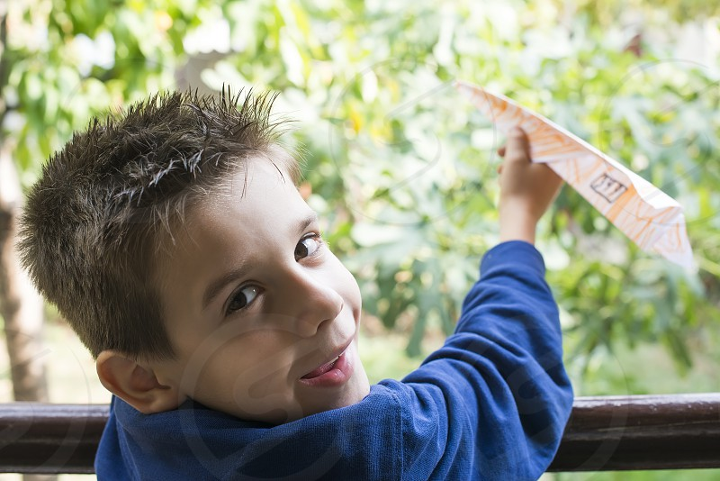 Kid throws paper plane. Authentic image photo