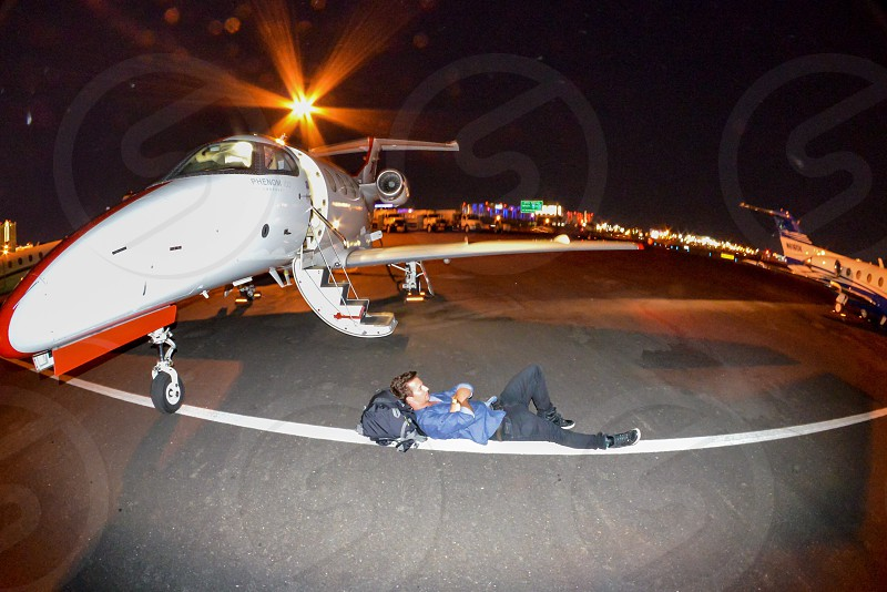 person wearing black pants lying on the ground near white aircraft photo