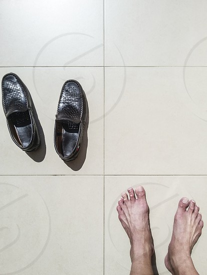 Top view of mens shoes and bare feet on titled floor  photo