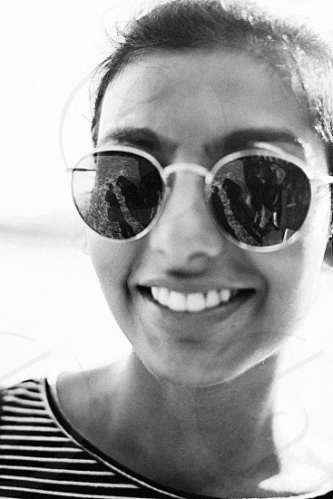 grayscale photography of woman wearing sunglasses taking selfie photo